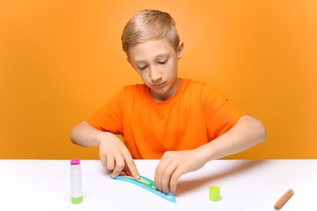 オレンジ色のtシャツを着た男の子が白いテーブルに座って、接着するための薄い紙片を準備します。子供はクイリングのテクニックを学びます