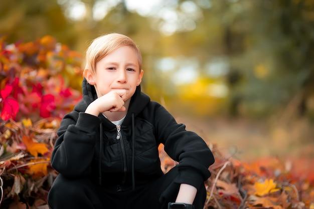 Мальчик в черной одежде прижал руку к щеке, сидит и скучает.