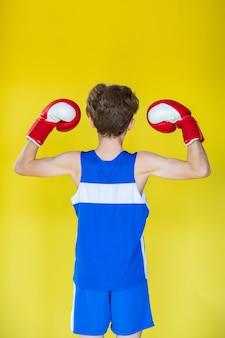 ボクシンググローブと黄色の背景に青い制服を着た少年