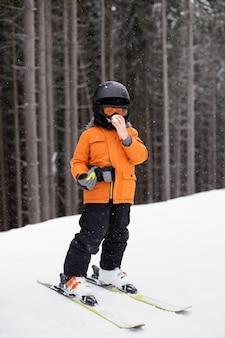 장비를 입은 소년이 눈 덮인 슬로프에서 보온병에서 차를 마신다