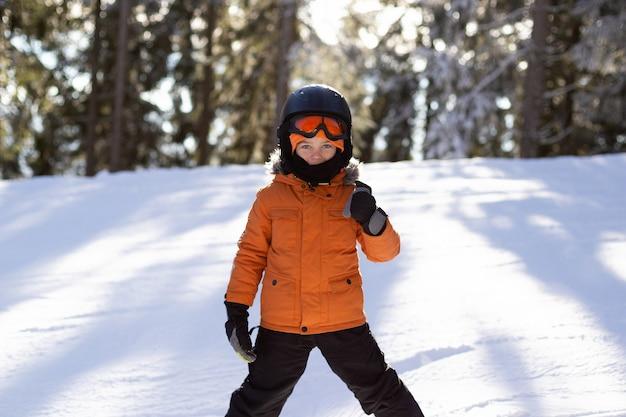 장비를 입은 소년이 눈 덮인 슬로프에서 스키를 타고 있다