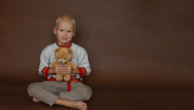 Мальчик в народной одежде с плюшевым мишкой, изолированным на коричневом фоне. концепция масленицы.
