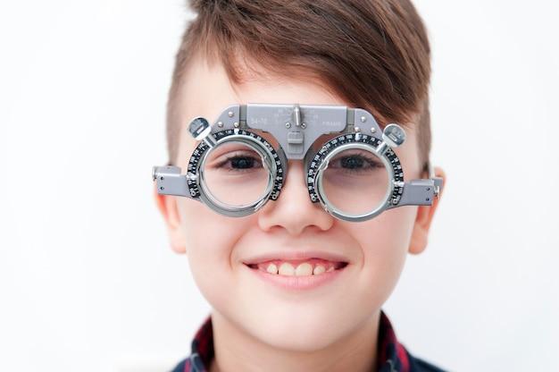 Мальчик в очках проверяет зрение у офтальмолога