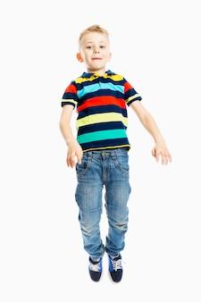 청바지와 여러 가지 빛깔의 티셔츠를 입은 소년이 점프합니다.