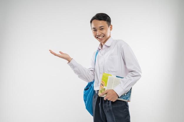 本を持っているときに手振りで何かを提供する中学生の制服を着た少年...