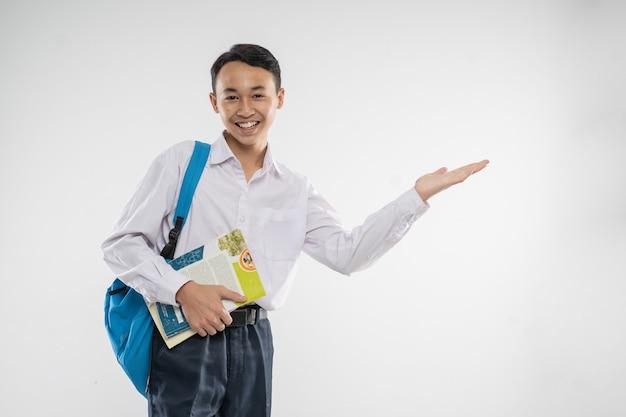 本を持っているときに手振りで何かを提供する中学生の制服を着た少年