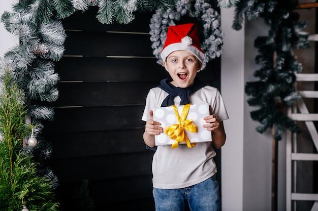 Мальчик в красной шляпе стоит с подарком в руках