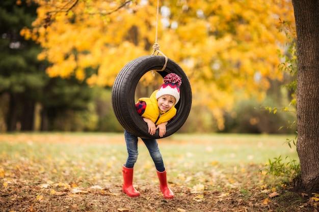Мальчик в красных резиновых сапогах садится за руль в осеннем парке