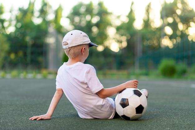 サッカーボールのサッカー場で緑の芝生の上に座っているスポーツ服の少年、背面図