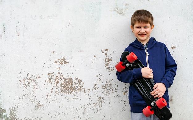 회반죽 벽을 배경으로 스케이트를 탄 운동복을 입은 소년.