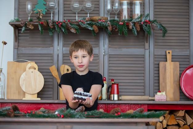自宅のクリスマスキッチンにいる男の子がケーキを手に持っています。