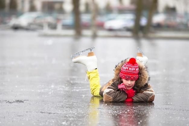 暖かい服とフィギュアスケートの男の子が氷の上に横たわっています。