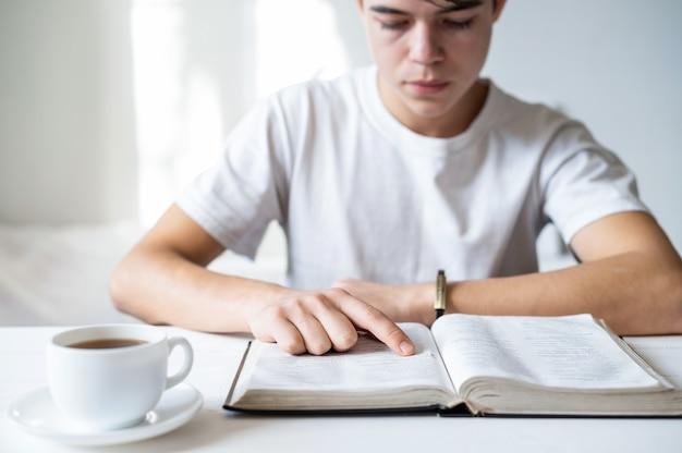 テーブルの上で本を読んでいる白いtシャツの少年、本の近くでufコーヒーをカップ