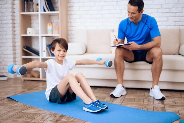 Мальчик делает упражнения с гантелями на полу.
