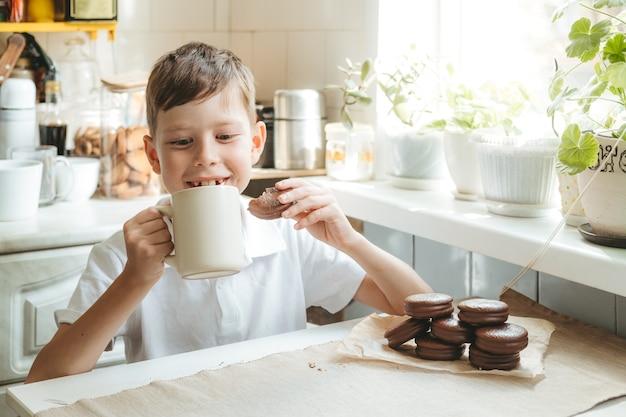 한 소년이 집 부엌에서 우유와 초콜릿 칩 쿠키를 마시고 있습니다. 행복한 아이는 흰색 컵에서 우유를 마시고 학교 케이크를 먹습니다.
