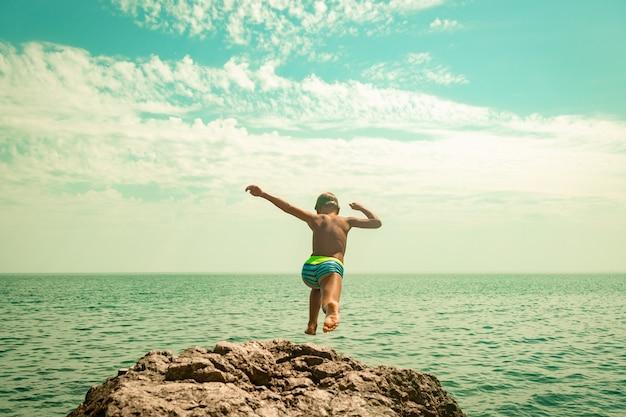 В жаркий летний день мальчик прыгает со скалы в море