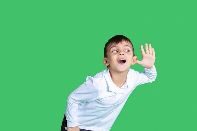 한 소년이 귀로 무언가를 듣고 있다 그는 흰색 셔츠가 녹색 배경을 입고 있는 모든 단어를 듣고 주의를 기울이고 있다