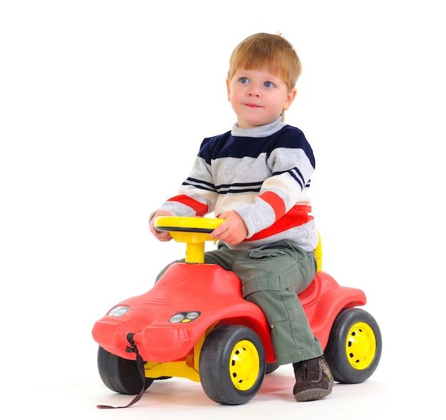 少年は孤立したおもちゃの車で遊ぶ