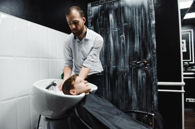 少年は理髪店の美容院で洗われる。
