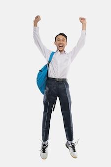 バックパックを背負って手を上げて笑っている中学生服を着た少年ジャンプ