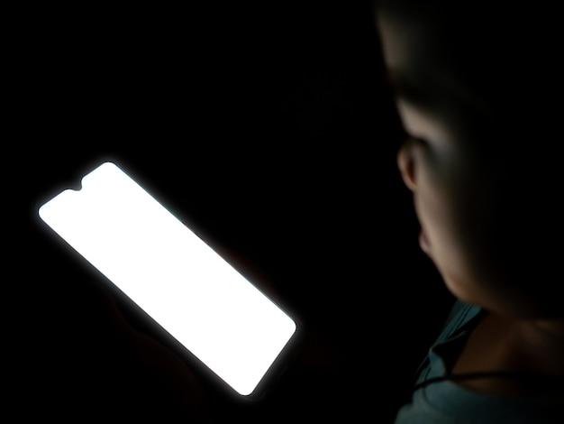 Мальчик смотрит на белый пустой экран телефона