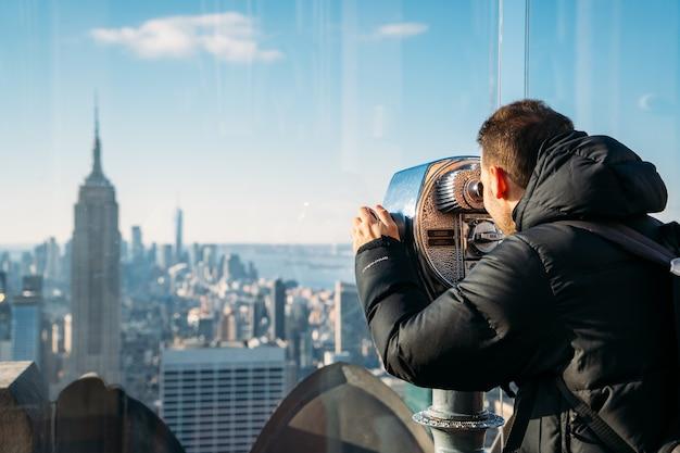 Мальчик наблюдает за нью-йорком в телескоп - крупный план.