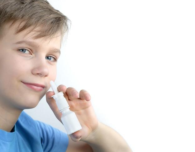 12세 소년이 비강 스프레이를 뿌립니다. 좋은 분위기에서 비강 스프레이를 사용하여 파란색 셔츠에 십대