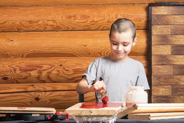 少年が田舎の家で赤い絵筆で木製の偽物を描く