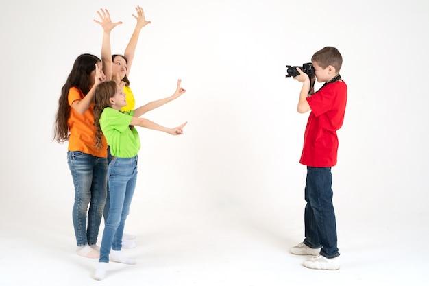 男の子の写真家がスタジオで白の3人のかわいい女の子の写真を撮ります