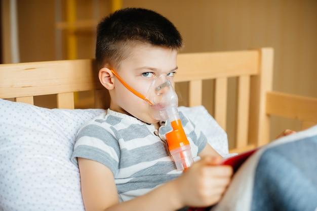 少年が肺吸入処置中にタブレットで遊ぶ