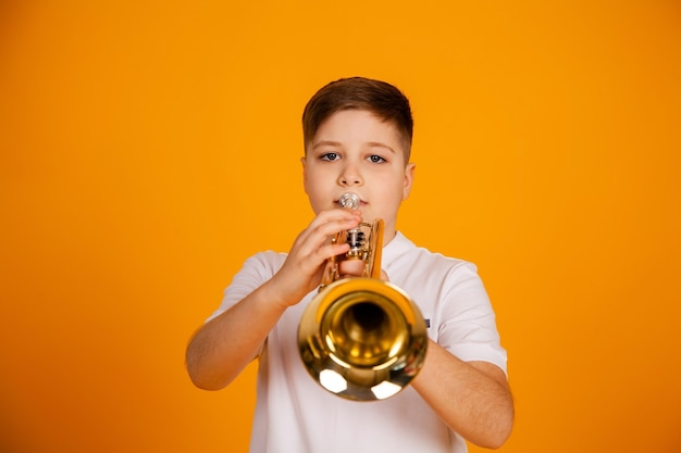 少年はトランペットを演奏します美しいティーンエイジャーの少年はトランペット楽器を演奏します
