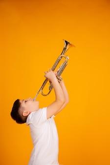 Мальчик играет на трубе. красивый подросток мальчик играет на музыкальном инструменте труба