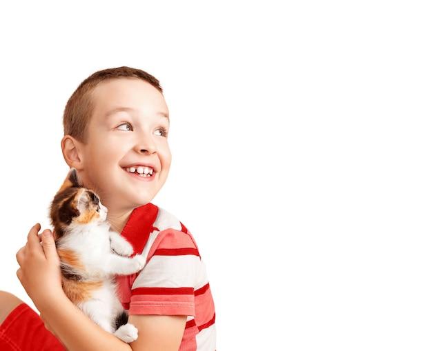 男の子は白い背景の上の斑点のある子猫の分離で遊ぶ