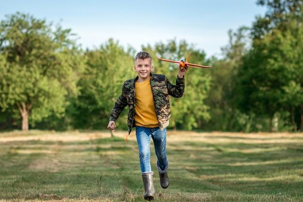 Мальчик бежит по полю и запускает игрушечный самолетик.