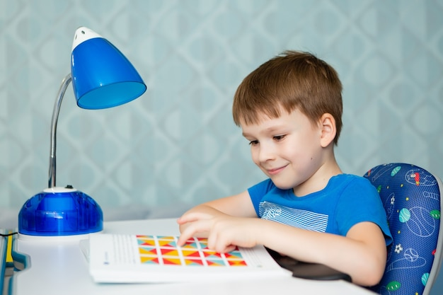 男の子の男子生徒がテーブルで本を注意深く勉強します。彼はレッスンを教えています