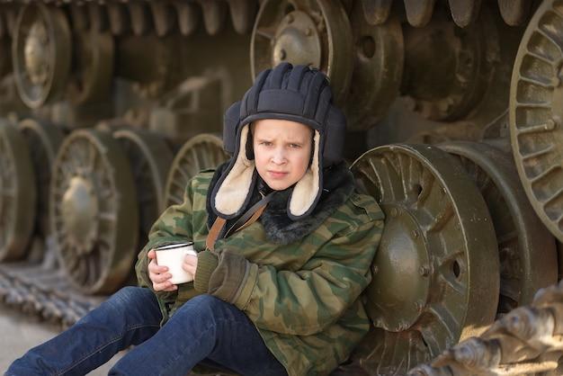 Мальчик сидит возле танка на улице в виде военного танкиста с кружкой в руках в зеленой форме