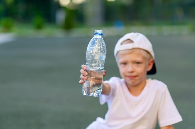 少年はサッカー場の緑の芝生に座って、水のボトルを持っています。水のボトルに焦点を当てます。