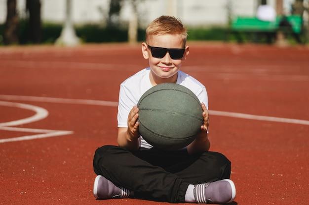 少年はバスケットボールをしてスポーツコートに座っています。高品質の写真