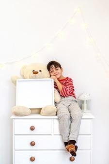 화장실에 앉아있는 소년과 테디 베어, 사진 프레임 및 양초가있는 흰색 가정 장식 세트 프리미엄 사진