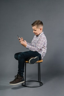 A boy sitting on stool using mobile phone against gray background