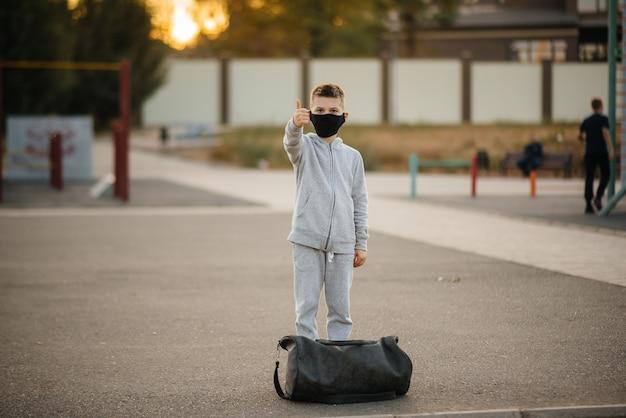 소년은 마스크를 쓰고 일몰 동안 야외 운동 후 스포츠 필드에 선다. 대유행 기간 동안 건강한 생활 방식.