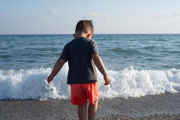 소년은 해변에 서서 파도와 바다를 즐깁니다.