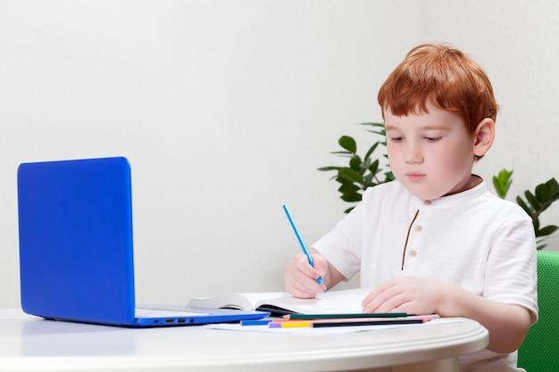 코로나 바이러스 대유행 중 학교 휴교 기간 동안 집에서 공부하는 소년