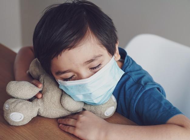 Pm2.5を保護するために医療用フェイスマスクを着用して胸の咳で疲れた少年、おもちゃで遊んでいる間に子供が眠りに落ちる、子供は保護コロナウイルス、インフルエンザの発生および病気の保護のため家にいる