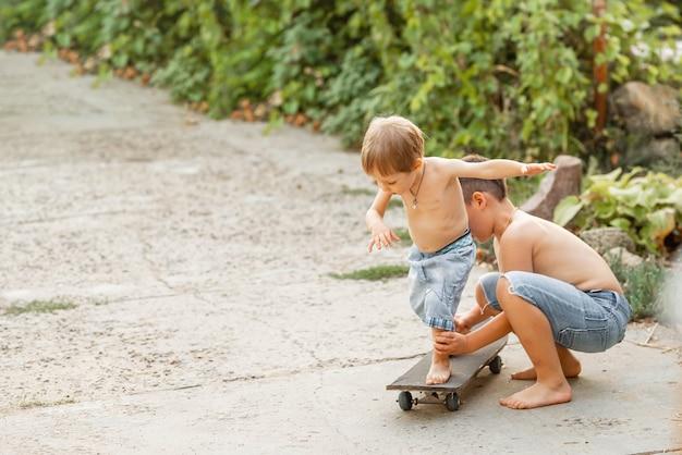 Мальчик тренируется кататься на роликовых коньках с другими детьми скейтбординга мальчика
