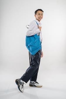 バックパックを背負って笑っている中学生服を歩いている少年