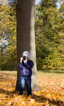Мальчик гуляет по парку и фотографирует свое окружение
