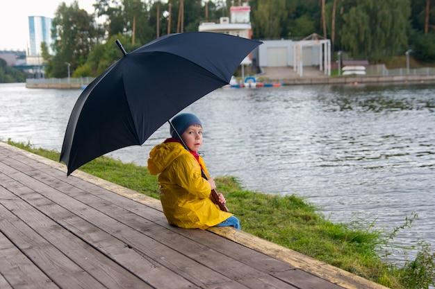 노란 비옷을 입고 우산 아래를 걷고 있는 소년. 구름 낀 날씨