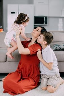 소년은 바닥에 집에서 여동생을 안고 그의 젊은 어머니를 지켜보고있다