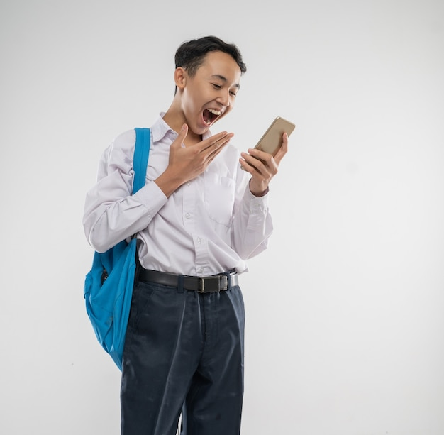 驚きの表情と身振りで携帯電話を持った中学生服を着た少年